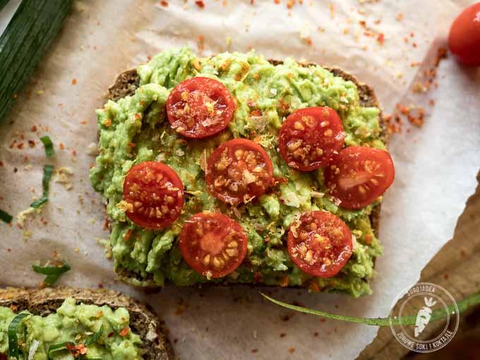 Kromki chleba posmaruj grubą warstwą masła z awokado. Na kanapkach ułóż przekrojone na pół pomidorki i udekoruj szczypiorem.